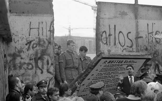 FILE - In this Nov. 11, 1989 file photo, East German border guards are seen through a gap in the Berlin wall after demonstrators pulled down a segment of the wall at Brandenburg gate, Berlin. The Berlin Wall is gone, but people can still tag their memories upon it online. The Berlin Twitter Wall, which went online Tuesday, Oct. 20, 2009 encourages people to share their memories of the wall's collapse and hopes for the future on a scrolling wall using Twitter, the social networking site. (AP Photo/Lionel Cironneau, File)